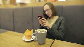 Muchacha sola en los vidrios que esperan a su novio de la otra persona Ella usando el app en smartphone en coco de consumición de metrajes