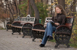 Muchacha sola en una lectura del parque Fotos de archivo