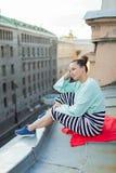 Muchacha sola hermosa que se sienta en el tejado en la ciudad vieja de sueños Imagenes de archivo