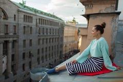 Muchacha sola hermosa que se sienta en el tejado en la ciudad vieja de sueños Imagen de archivo