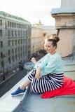 Muchacha sola hermosa que se sienta en el tejado en la ciudad vieja de sueños Imágenes de archivo libres de regalías