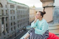 Muchacha sola hermosa que se sienta en el tejado en la ciudad vieja de sueños Fotografía de archivo