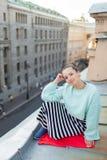 Muchacha sola hermosa que se sienta en el tejado en la ciudad vieja de sueños Foto de archivo libre de regalías