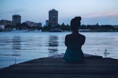 Muchacha sola mirando la ciudad por el agua Imagenes de archivo