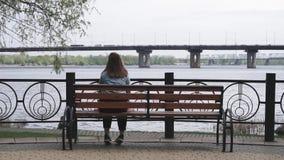 Muchacha sola que se sienta en el banco en el parque y que mira en el paisaje industrial metrajes