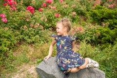 Muchacha sola que se sienta en la piedra en parque imagen de archivo libre de regalías