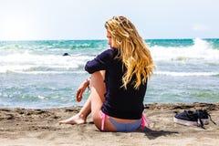 Muchacha sola que se sienta en la playa con el mar Pensativo y cariñoso Decepción en amor Fotos de archivo