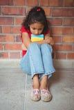Muchacha sola trastornada que se sienta sola Foto de archivo libre de regalías