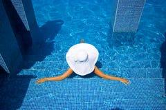 Muchacha, sombrero blanco y piscina Foto de archivo