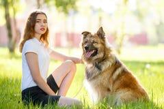 Muchacha sonriente adolescente con su perro que se sienta en parque Foto de archivo