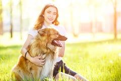Muchacha sonriente adolescente con su perro que se sienta en parque Fotos de archivo