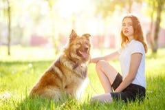Muchacha sonriente adolescente con su perro que se sienta en parque Imagenes de archivo