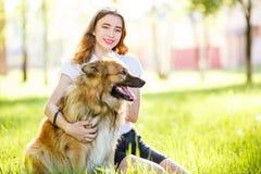 Muchacha sonriente adolescente con su perro que se sienta en parque Fotografía de archivo libre de regalías