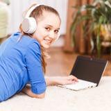 Muchacha sonriente adolescente que usa el ordenador portátil en el piso Imagen de archivo
