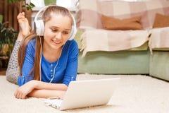 Muchacha sonriente adolescente que usa el ordenador portátil en el piso Imagenes de archivo