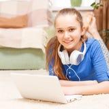 Muchacha sonriente adolescente que usa el ordenador portátil en el piso Fotos de archivo libres de regalías
