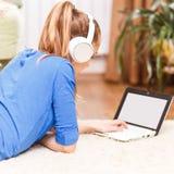 Muchacha sonriente adolescente que usa el ordenador portátil en el piso Foto de archivo