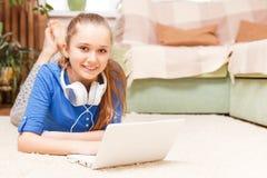 Muchacha sonriente adolescente que usa el ordenador portátil en el piso Foto de archivo libre de regalías