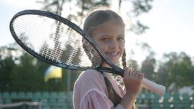 Muchacha sonriente adorable del retrato pequeña con coletas y una estafa de tenis en su hombro que mira en la situación de la cám almacen de metraje de vídeo