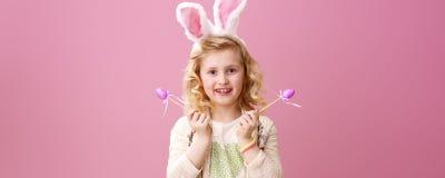 Muchacha sonriente aislada en rosa con los huevos de Pascua hechos a mano púrpuras Imágenes de archivo libres de regalías