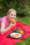 Muchacha sonriente al aire libre en el parque que tiene comida campestre foto de archivo
