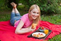 Muchacha sonriente al aire libre en el parque que tiene comida campestre imagen de archivo libre de regalías