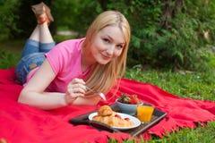 Muchacha sonriente al aire libre en el parque que tiene comida campestre fotos de archivo libres de regalías