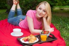 Muchacha sonriente al aire libre en el parque que tiene comida campestre fotografía de archivo libre de regalías