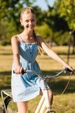 Muchacha sonriente alegre del adolescente que monta su bicicleta Imágenes de archivo libres de regalías