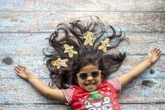 Muchacha sonriente alegre linda con el pelo adornado de la Navidad fotos de archivo libres de regalías
