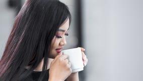 Muchacha sonriente asiática joven encantadora que sostiene la taza blanca grande las manos y gozando de la bebida caliente metrajes
