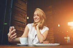 Muchacha sonriente atractiva del inconformista que hace el autorretrato en el teléfono de célula mientras que se sienta en café Foto de archivo