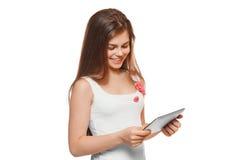 Muchacha sonriente atractiva en la camisa blanca usando la tableta Adolescente con la PC de la tableta, aislada en el fondo blanc Imágenes de archivo libres de regalías