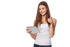 Muchacha sonriente atractiva en la camisa blanca usando la tableta que muestra los pulgares para arriba Mujer con la PC de la tab Imágenes de archivo libres de regalías