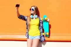 Muchacha sonriente bastante fresca en gafas de sol con el monopatín que toma el autorretrato de la imagen en smartphone Fotografía de archivo libre de regalías