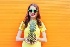Muchacha sonriente bastante fresca en gafas de sol con la piña sobre naranja colorida Foto de archivo libre de regalías