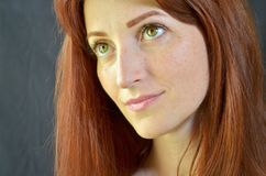Muchacha sonriente blanca con el pelo rojo y los ojos verdes con extensiones de la pestaña en el fondo gris que mira para arriba fotografía de archivo libre de regalías