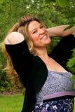 Muchacha sonriente bonita con el pelo rubio largo rizado Foto de archivo libre de regalías
