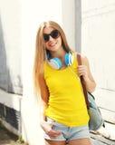 Muchacha sonriente bonita con los auriculares y la mochila Fotos de archivo libres de regalías