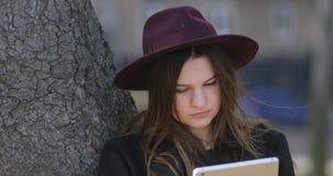 Muchacha sonriente bonita del inconformista que se relaja en el parque y que usa la tableta 4k, steadicam metrajes