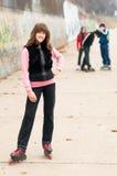 Muchacha sonriente bonita en la presentación de los rollerskates al aire libre con los amigos Imagen de archivo