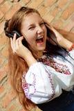 Muchacha sonriente bonita que canta en auriculares Imágenes de archivo libres de regalías