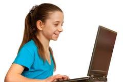 Muchacha sonriente bonita que estudia con la computadora portátil Foto de archivo