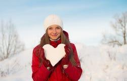 Muchacha sonriente bonita que lleva a cabo un corazón de la nieve. Amor. imágenes de archivo libres de regalías