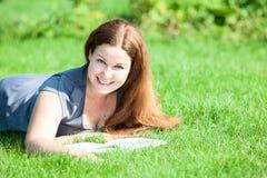 Muchacha sonriente bonita que miente en hierba verde con el libro abierto Imágenes de archivo libres de regalías