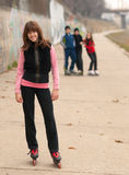 Muchacha sonriente bonita que presenta afuera con los amigos Foto de archivo