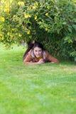 Muchacha sonriente bonita que se relaja en la hierba Fotografía de archivo libre de regalías
