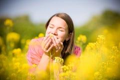Muchacha sonriente bonita que se relaja en las flores amarillas Foto de archivo libre de regalías