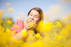 Muchacha sonriente bonita que se relaja en las flores amarillas Fotos de archivo