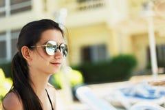 Muchacha sonriente bonita que sienta un poolside piscina y ho Fotos de archivo libres de regalías